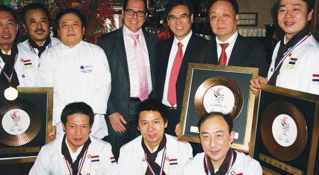 获奖厨师手持奖牌与庆功宴与会嘉宾合影